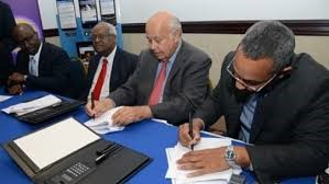 Gleaner & RJR execs signing merger agreement earlier in 2015